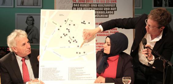 """Thomas Laue vom Schauspiel zeigt, wo am 14. Juni bei """"Birlikte 2"""" etwas los ist. OB Jürgen Roters und Meral Sahin (IG Keupstraße) halten die Karte. Foto: Jürgen Schön"""