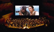 Fluch der Karibik flimmert auf der Leinwand, während ein Orchester für musikalische Untermalung sorgt.