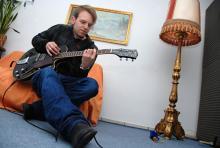 """Singt, spielt Gitarre und schreibt die Songs für Neuser: Namensgeber Henning Neuser im """"Kreativraum"""" in Nippes. (Foto: Helmut Löwe)"""