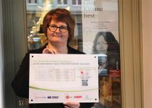 """Die Nippeser Buchhändlerin Dorothee Juck darf ihr Geschäft als erste mit dem Teilnehmerschild """"Klimastraße Neußer Straße"""" schmücken. Foto: Jürgen Schön"""