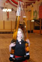 Bewaffnet mit zehn Litern Kölsch: Lara Brovot zeigt, wie das Bier an die Tische transportiert wird. (Foto: Helmut Löwe)