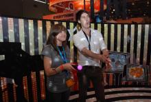 """Der Spieleentwickler von """"TV Superstars"""" erklärt koeln.de Reporterin Klaudia Fernowka die neue Steuerung mit dem Move-Motion-Controller."""