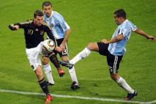 Lukas Podolski (l.) im Zweikampf mit Argentiniens Nicolas Otamendi (r.) und Walter Samuel. Foto: ddp.