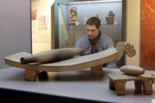Der Pädagoge des Schokoladenmuseums, Olaf Vortmann, betrachtet ein historisches Reibebrett aus Mexiko (Foto: dapd)