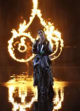 Aufwendige Bühneninszenierung: Sopranistin Csilla Csövári vor feurigen Zeichen auf einer Wasserbühne