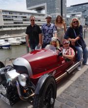 Der etwas andere Schlitten: Schwarz, Engel und vier seiner Bandmitglieder im schicken, roten Morgan (Foto: Cora Finner)