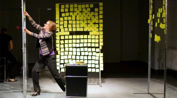 Satire über Selbstausbeutung und Karrieredenken: Gelbe Post-its und Notebooks sind Annes (Johanna Paliatsou) beste Freunde. Foto: MeyerOriginals / FWT